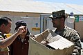 U.S. Army Capt. Syed Ali, right, with a regional communications center with Combined Joint Task Force (CJTF) 101, 101st Airborne Division, with prepares to distribute school items to Afghan children at the El 130827-A-YW808-001.jpg