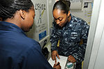 U.S. Navy Legalman 3rd Class Tiffany Williams, right, shows Boatswain's Mate 2nd Class Jessica Shockley how to fill out a power of attorney form in the legal office aboard USS George H.W. Bush (CVN 77) in 110707-N-QL471-028.jpg