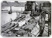 A large battleship in dock; the ship is covered with scaffolding, ladders, and other construction equipment.