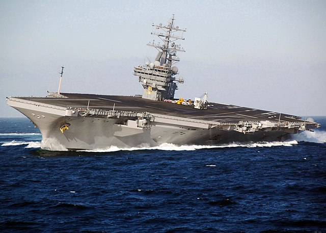 CVN-76 nuclear carrier listing to port under hard rudder at full speed