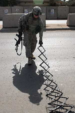 Spike strip - A U.S. Army soldier deploying a spike strip at a vehicle checkpoint in Iraq