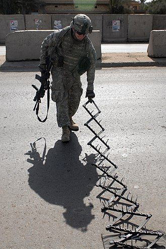 Spike strip - A U.S. Army soldier deploying a stinger at a vehicle checkpoint in Iraq