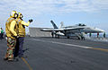 US Navy 030314-N-6895M-515 Aviation Boatswain's Mates direct an F-A-18C Hornet into launching position on the flight deck.jpg