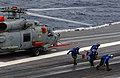 US Navy 030906-N-3005E-047 Four chock and chain handlers dash away from an SH-60B Sea Hawk helicopter.jpg
