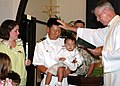 US Navy 050711-N-5783F-001 Lt. Cmdr. Chris Buziak is blessed by Father Patrick McCormick during a baptism ceremony for his son held at Pearl Harbor Memorial Chapel.jpg