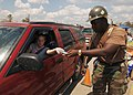 US Navy 050908-N-4374S-010 A U.S. Navy Seabee, Builder 3rd Class Bobby Fullard, assigned to Naval Mobile Construction Battalion Seven (NMCB-7), distributes relief supplies to a resident of Harrison County.jpg