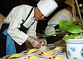 US Navy 060509-N-3560G-015 Culinary Specialist 3rd Class Guangfeng Zhou assigned to Naval Mobile Construction Battalion Four (NMCB-4) prepares food to be used in a competition dinner.jpg
