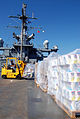 US Navy 080819-N-6544L-001 Able Seaman Frank Santana, a Military Sealift Command civilian, moves pallets of humanitarian relief supplies aboard the amphibious command ship USS Mount Whitney (LCC-JCC 20).jpg