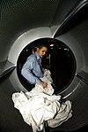 US Navy 081103-N-6538W-032 hip's Serviceman Seaman Apprentice Kyle Estrella removes bed sheet linens from a dryer.jpg