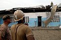 US Navy 090421-N-7948C-041 Construction Electrician 2nd Class Darius Michael assigned to Naval Mobile Construction Battalion (NMCB) 11 removes a piece of aluminum from the top of Balise Elementary School in Port Gentil.jpg
