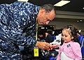 US Navy 110324-N-4044H-051 Cmdr. Robert J. Thomas entertains a child while her family waits for further instructions after passing through customs.jpg