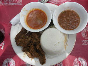 Ugandan cuisine - Posho or Ugali consists of maize flour (cornmeal) cooked with water to a porridge- or dough-like consistency. Pictured on the bottom-right of the plate, its served with beef and sauce.