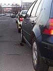 Beschädigter Rückspiegel an einem geparkten Auto, die Spiegelkappe liegt am Boden.