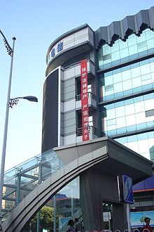 "A vertical, red banner hanging high on a building with Chinese writing: ""维护法律尊严,严惩犯罪分子"""