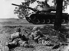 Du soldatoj kaŭras sub arbo dum tanko sidas sur vojo antaŭ ili.