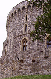A photograph showing the left hand side of a circular stone tower made of grey stone and with small windows.