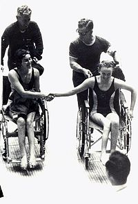 Australian Paralympic Team members Daphne Ceeney (now Hilton) and Elizabeth Edmondson shake hands after Edmondson won gold and Ceeney silver in the 50m prone swimming event at the 1964 Tokyo Paralympic Games. They are pushed by Kevin Betts (Ceeney) and 'Johnno' Johnston (Edmondson)