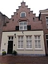foto van Huis met topgevel met ontlastende korfboog om bovenvenster