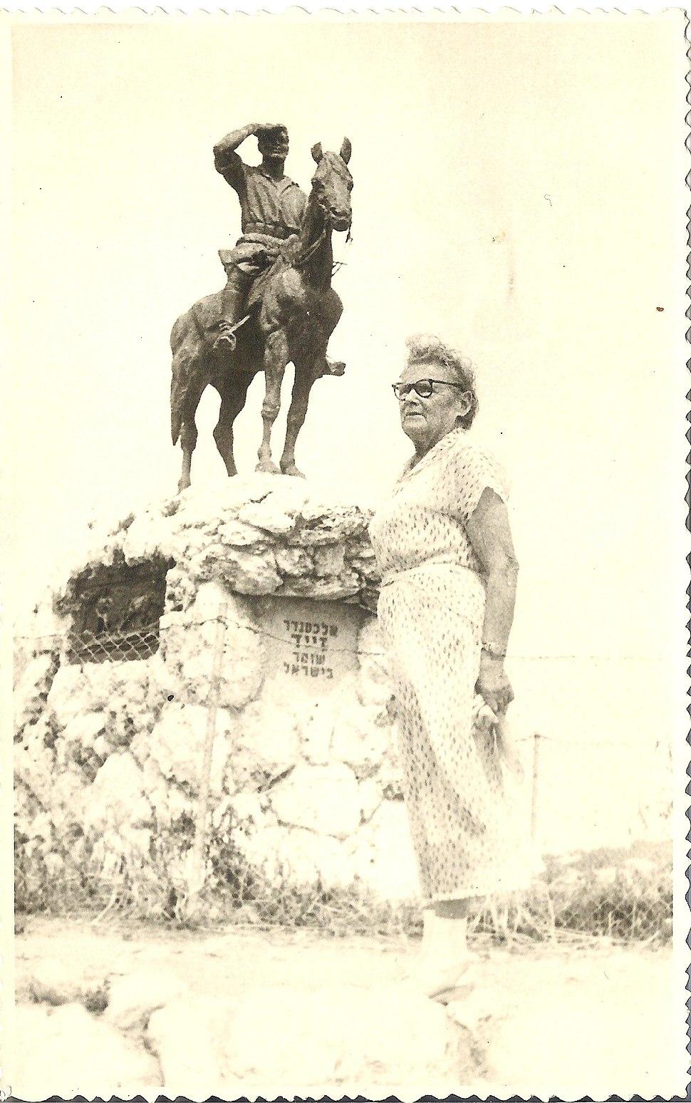 ציפורה זייד בתמונה ליד האנדרטה של בעלה המנוח אלכסנדר זייד