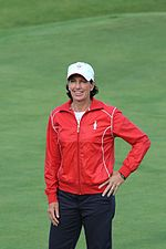 A brown-haired woman in a red jacket and navy blue pants and white undershirt and white hat