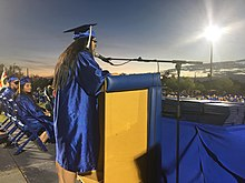 Student speaks to audience at graduation ceremony.