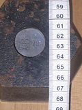 A hexagonal 2kg weight – bottom view showing lead plug and assayer's stamp