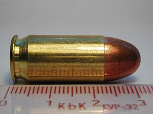Caliber - Side on view of Sellier & Bellot .45-cal ACP cartridge with a metric ruler for scale