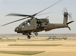 Photo of tilted horizon showing helicopter flying above barren land with rectangular patches of green grass.