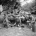A Cromwell tank crew of 4th County of London Yeomanry, 7th Armoured Division, preparing a meal in front of their vehicle, Normandy, 17 June 1944. B5681.jpg