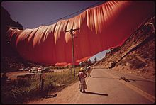 An enormous volume of fabric hangs from a wire across a valley. I the foreground is a telephone pole and several people looking up.