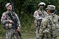 A Soldier from the 10th Combat Aviation Brigade, talks with Soldiers from the Latvian National Guard.jpg