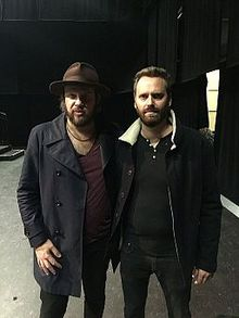 Two members of the band standing beside each other backstage.