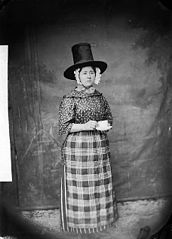A woman in national dress and drinking tea