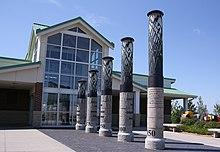 Cinco pilares conducen a un edificio con una pared de ventanas.