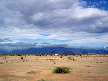 Desert under mostly cloudy sky, with hills in background