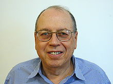 Shoulder high portrait of man in his sixties in a checked shirt with a blank white background