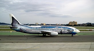 Right side view of an aircraft taxiing on the ground with a giant salmon painted on the fuselage.