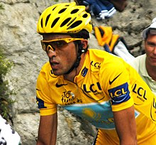 Close-up of a cyclist in a yellow jersey, wearing yellow-rimmed sunglasses and a yellow helmet. His bicycle is not visible, but he is in riding position. A spectator is partly visible behind him.