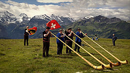 Four alp horn players on a grassland, with Swiss flags waving behind them and high mountains in the background