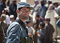 An Afghan National Civil Order Police (ANCOP) officer provides security as U.S. Marines assigned to Police Adviser Team Delaram observe other ANCOP officers distributing radios and comic books to residents 130526-M-RO295-185.jpg