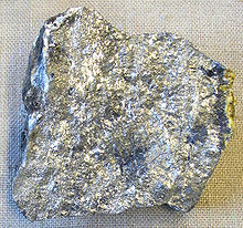An irregular piece of silvery stone with spots of variation in luster and shade.