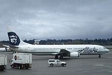 Right side view of an airplane taxiing on the tarmac, with several trucks in the foreground and to the left. In the background is a tree-covered hill and dark clouds.