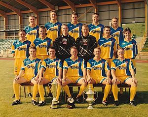 Barry Town United F.C. - The Barry squad of 1999 at Jenner Park, with the League of Wales Cup, FAW Premier Cup and Welsh Premier League trophies.