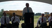 Transportation Secretary Ray LaHood stands at a podium flanked by Arkansas state officials and addresses those attending the groundbreaking with a large dump truck in the background