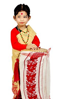 Girl in traditional Mekhela chador dress with aDhol wrapped with Gamosa Bihu Assam.jpg