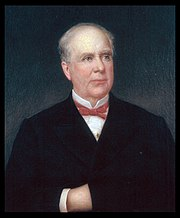 A balding man with white hair wearing a white shirt and black coat and bowtie