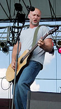 Full length portrait, wearing gray t-shirt and blue jeans, no hair, short gray beard, playing electric guitar.