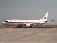 Boeing 737-400 with a white body, metallic belly and a red cheatline