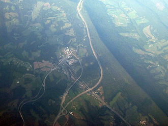 Breezewood, Pennsylvania - Oblique air photo of Breezewood and vicinity, facing northeast, and showing Interstate 70, the Pennsylvania Turnpike, U.S. Route 30, and Rays Hill. The Abandoned Pennsylvania Turnpike can also be seen paralleling the Turnpike northeast of Breezewood.