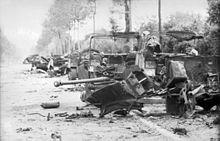 Several wrecked vehicles along the verge of a tree and hedge lined road. A destroyed gun, twisted metal and debris occupy the foreground.